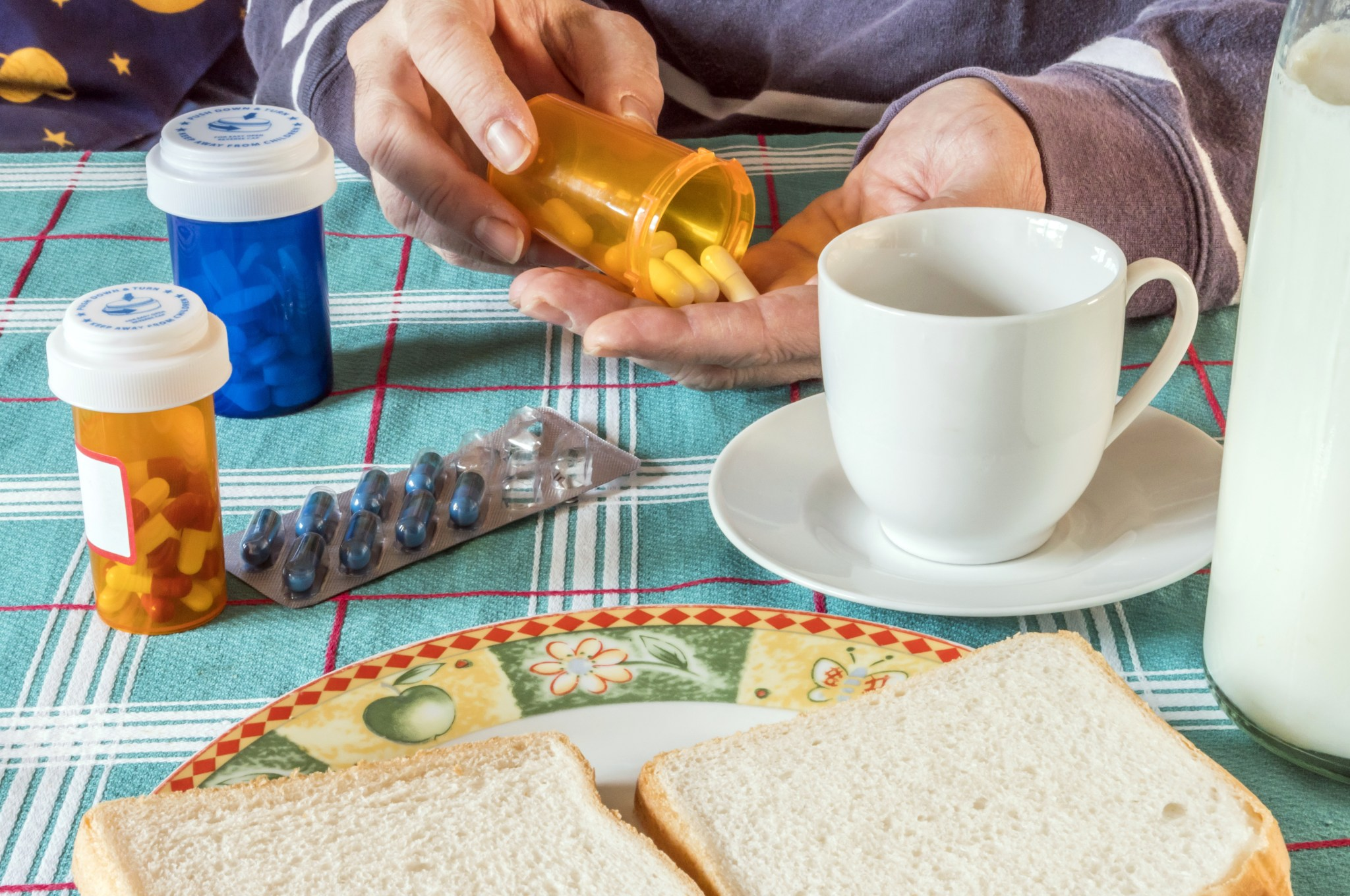 Person takes medication during breakfast, conceptual image